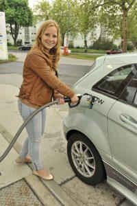 Eine Frau tankt ein Wasserstoffauto