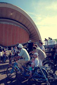 Radfahrer auf stehenden Fahrrädern, im Hintergrund das Berliner Haus der Kulturen der Welt